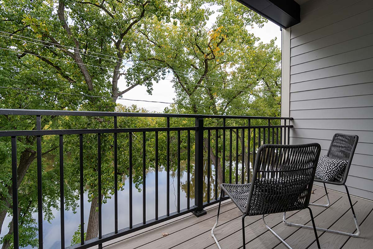 2 chairs outside on balcony overlooking the river