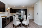 modern kitchen with dark wood cabinet and small table with four chairs